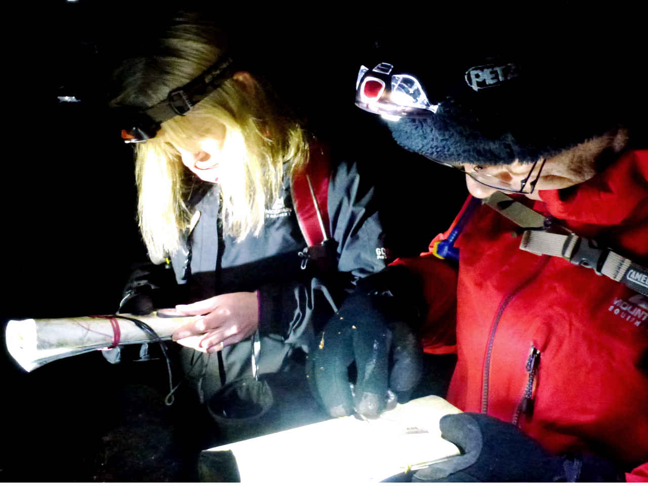 Head torches light up a map and compass during a night navigation low visibility course on New Forest heathland