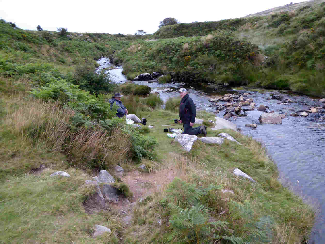 group cook a tasty meal by a river on dartmoor