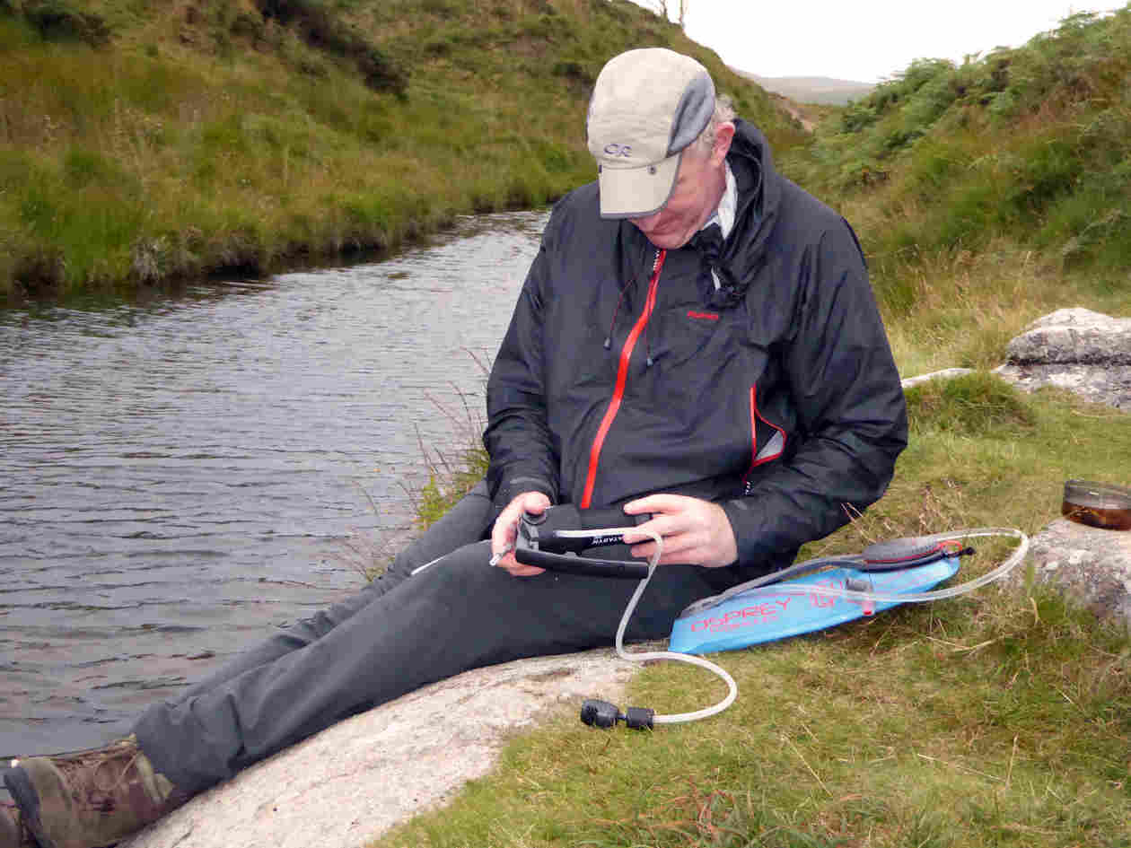 man learning how to use a water purifier to collect and treat water wild camping on dartmoor