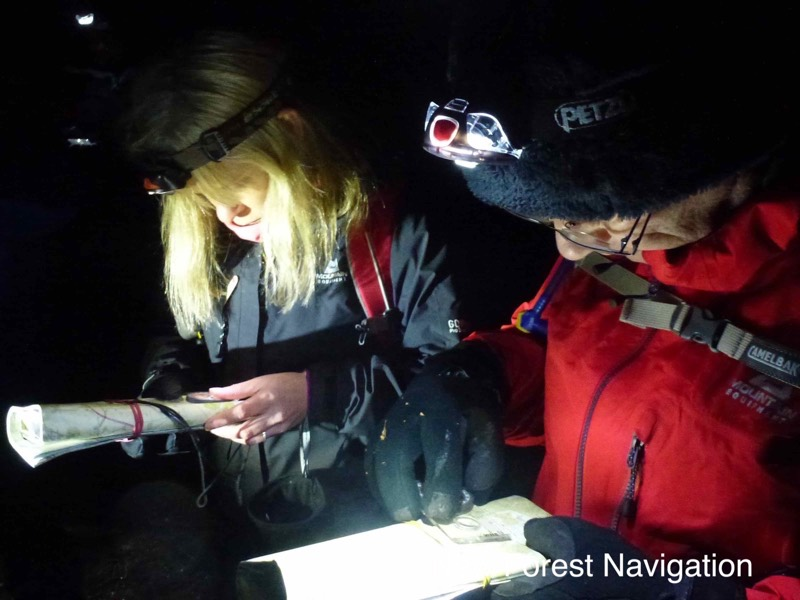 head torches light up maps and compasses on a night navigation course