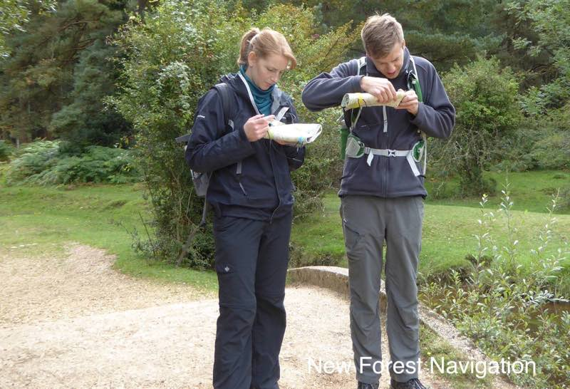 two people use prcise navigation and compass to check path direction