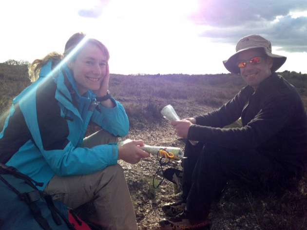 backpacking couple rest on a new forest heathland path