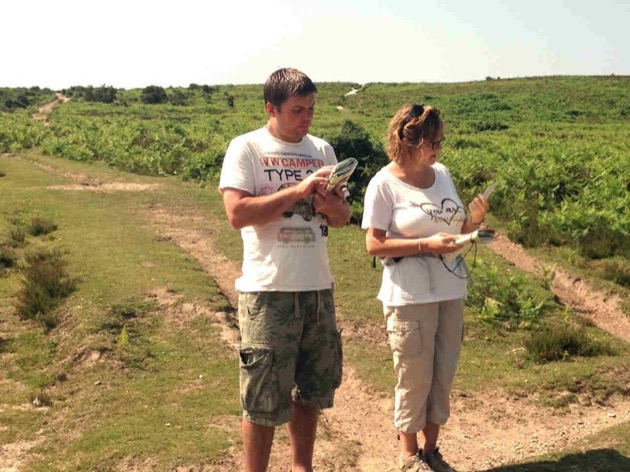 couple learning to use maps and compasses in open heathland