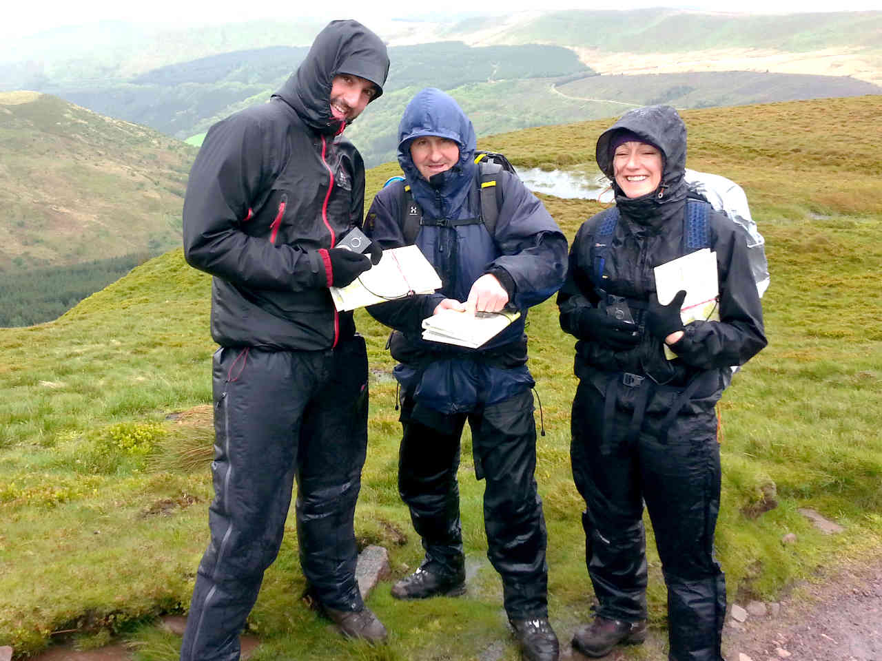 very wet and windy map reading group on mountain ridge smile at the camera