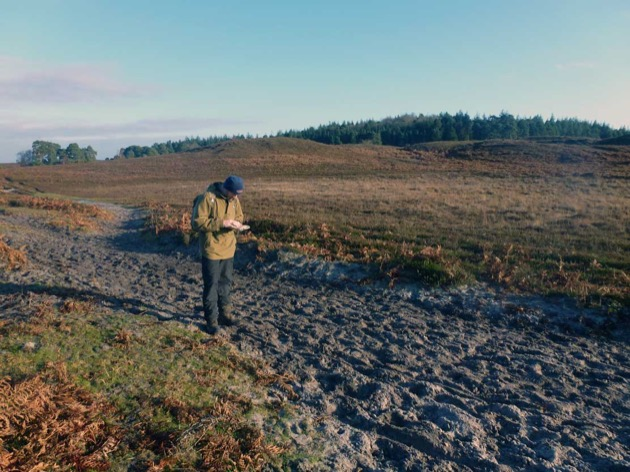 man with heathland back drop uses compass to selct correct path
