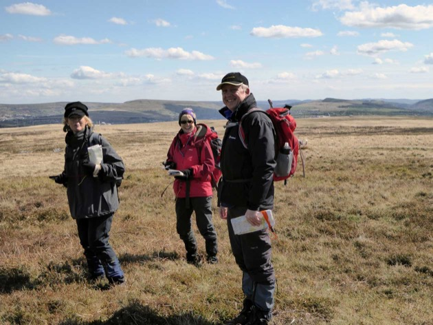 group using maps and compasses on high moorland in wales