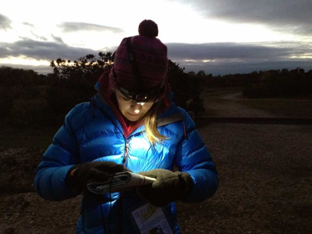 lady at dusk check map using a head torch to plan low visibility route