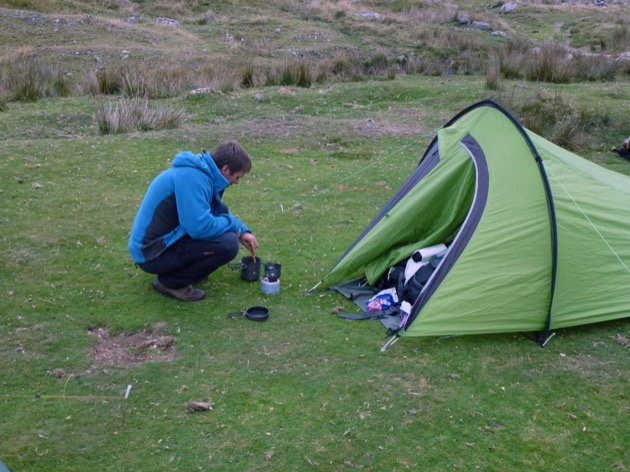person learning to use small backpacking stove to prepare a hot meal while wild camping