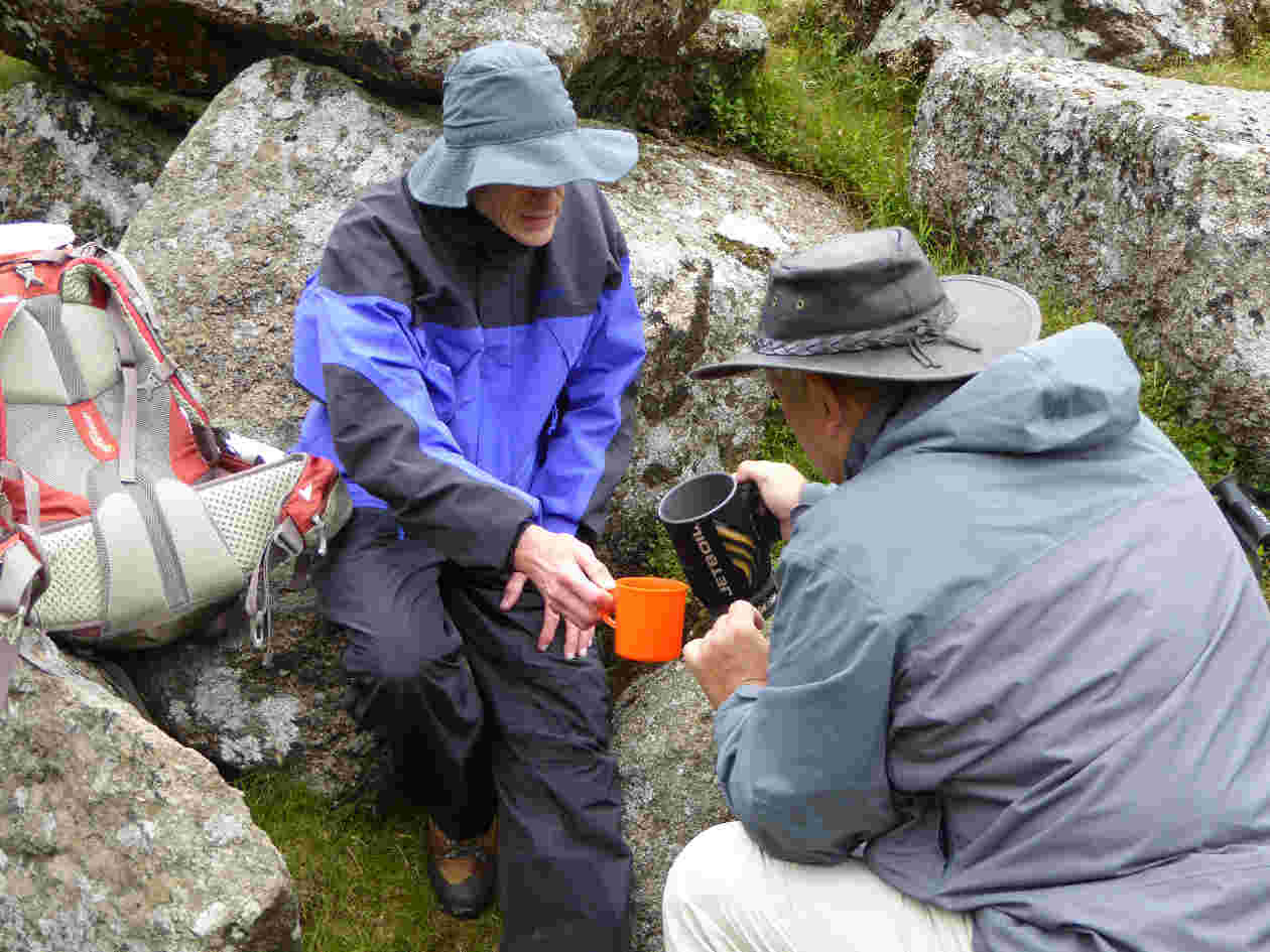 wild campers share a hot drink on a rest stop on dartmoor